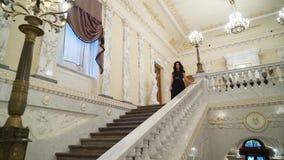 Giovane donna castana sexy in vestito uguagliante nero che va di sotto alla scala di pietra di marmo in palazzo o in hotel video d archivio