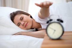 Giovane donna castana sonnolenta che allunga mano al giro disposto di squillo dell'allarme fuori Presto svegli, non ottenendo abb Fotografia Stock Libera da Diritti