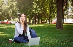 Giovane donna castana sorridente su un'erba, lavorando con il computer portatile e parlando sul telefono nel parco Immagini Stock Libere da Diritti
