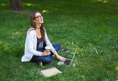 Giovane donna castana sorridente in vetri su un'erba, lavorante con il computer portatile nel parco Immagini Stock