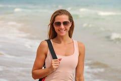 Giovane donna castana sportiva in occhiali da sole, stanti sulla spiaggia, mare azzurrato dietro lei, sole leggermente che splend fotografie stock