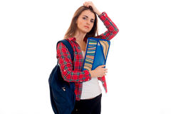 Giovane donna castana stanca dello studente con lo zaino blu sulla sua spalla e cartella per i taccuini in mani che esaminano Immagini Stock Libere da Diritti