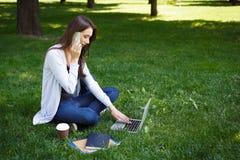 Giovane donna castana su un'erba, lavorante con il computer portatile e parlante sul telefono nel parco Immagine Stock Libera da Diritti