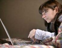 Giovane donna castana sveglia che si trova sul letto e che scrive in suo computer portatile immagine stock