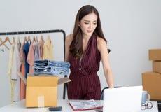 Giovane donna casuale asiatica che lavora piccola impresa per controllare il suo ordine in computer portatile e che imballa i jea fotografie stock libere da diritti