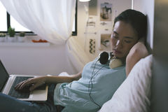 Giovane donna casuale che dorme sul letto mentre per mezzo del computer portatile a casa Fotografia Stock