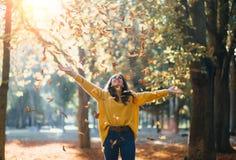 Giovane donna casuale che gode della stagione di autunno al parco della città immagini stock libere da diritti