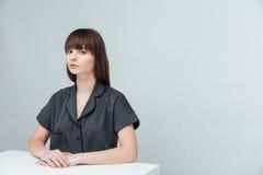 Giovane donna casuale che si siede allo scrittorio Fotografia Stock Libera da Diritti