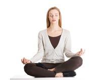 Giovane donna casuale che si siede e che fa yoga Immagine Stock