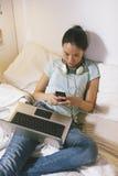 Giovane donna casuale che si siede sul letto e che per mezzo dello Smart Phone a casa Fotografie Stock