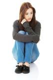 Giovane donna casuale che si siede sul pavimento bianco fotografia stock libera da diritti