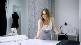 Giovane donna casuale che sta alla tavola e che lavora nell'atelier stock footage