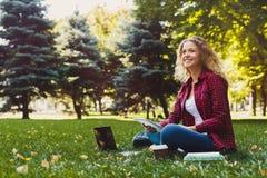 Giovane donna casuale con il computer portatile ed il taccuino all'aperto Fotografia Stock