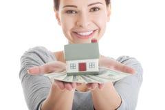 Giovane donna casuale con soldi e la casa. Fotografia Stock