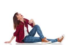 Giovane donna casuale di risata che si siede su un pavimento Immagini Stock