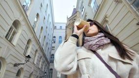 Giovane donna casuale graziosa che gode bevendo la tazza di carta del caffè all'aperto fra la casa europea tipica archivi video
