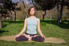 Giovane donna caucasica in buona salute che fa esercizio di forma fisica di yoga al parco fotografie stock libere da diritti