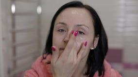 Giovane donna caucasica che applica maschera crema sul fronte Procedura facciale della stazione termale a casa archivi video