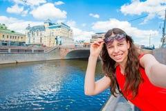 Giovane donna caucasica che fa selfie sul fondo delle attrazioni all'aperto La ragazza felice gode del suo fine settimana in citt Fotografie Stock Libere da Diritti