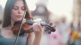 Giovane donna caucasica che gioca le fiddle sulla via pedonale al giorno di estate archivi video