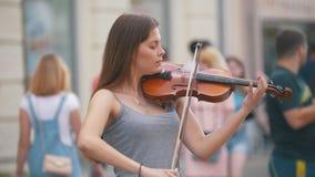 Giovane donna caucasica che gioca le fiddle sulla via pedonale al giorno di estate video d archivio
