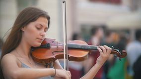 Giovane donna caucasica che gioca le fiddle sulla via pedonale al giorno di estate stock footage