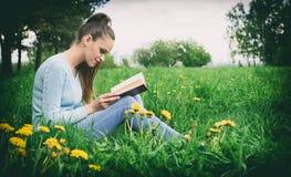 Giovane donna caucasica che legge un libro all'aperto Immagini Stock