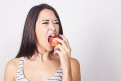 Giovane donna caucasica che mangia una mela Fotografie Stock Libere da Diritti