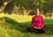 Giovane donna caucasica che medita all'aperto Immagine Stock