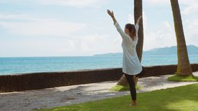 Giovane donna caucasica che si rilassa praticando yoga sulla spiaggia vicino all'oceano calmo sull'isola Bali con bello fondo video d archivio