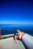 Giovane donna caucasica che si siede davanti ad una barca Immagine Stock Libera da Diritti