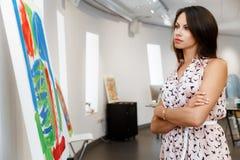 Giovane donna caucasica che sta nella parte anteriore della galleria di arte delle pitture Fotografie Stock Libere da Diritti