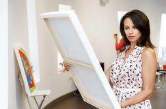 Giovane donna caucasica che sta nella parte anteriore della galleria di arte delle pitture Fotografia Stock