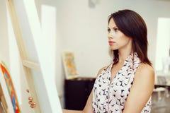 Giovane donna caucasica che sta nella parte anteriore della galleria di arte delle pitture Immagine Stock