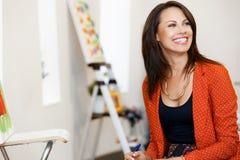 Giovane donna caucasica che sta nella parte anteriore della galleria di arte delle pitture Immagini Stock