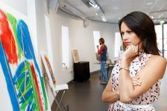 Giovane donna caucasica che sta nella parte anteriore della galleria di arte delle pitture Immagini Stock Libere da Diritti