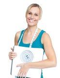 Giovane donna caucasica che tiene una scala del peso Immagini Stock