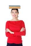 Giovane donna caucasica con il libro sulla sua testa Immagini Stock Libere da Diritti