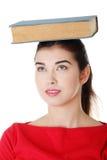 Giovane donna caucasica con il libro sulla sua testa Fotografie Stock