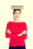 Giovane donna caucasica con il libro sulla sua testa Immagine Stock Libera da Diritti