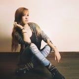 Giovane donna caucasica con il tatuaggio trasversale su una mano che si siede su un pavimento Fotografia Stock Libera da Diritti