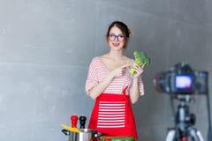 Giovane donna caucasica di blogger che cucina l'alimento del vegano immagini stock