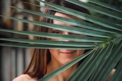 Giovane donna caucasica misteriosa che si nasconde dietro la foglia di palma fotografia stock libera da diritti