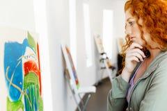 Giovane donna caucasica nella parte anteriore della galleria di arte delle pitture Fotografia Stock