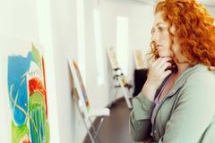 Giovane donna caucasica nella parte anteriore della galleria di arte delle pitture Immagine Stock Libera da Diritti