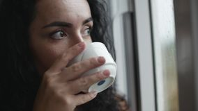 Giovane donna caucasica pensierosa che esamina la pioggia fuori del caffè bevente della finestra archivi video