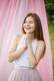 giovane donna caucasica sorridente con capelli rossi lunghi in maglietta bianca che si rilassa nel parco su fondo rosa Fotografie Stock