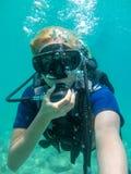 Giovane donna caucasica vestita nel nuoto dell'attrezzatura per l'immersione subacqueo in mare ionico Immersione con bombole dell fotografie stock libere da diritti