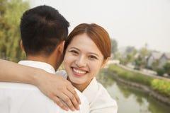 Giovane donna che abbraccia il suo ragazzo Immagine Stock