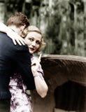 Giovane donna che abbraccia un uomo e che indica verso un bordo di informazioni (tutte le persone rappresentate non sono vivente  Fotografie Stock